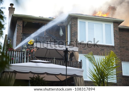 BRAMPTON, ONTARIO -  JULY 20 2012 - Firefighters attempt to douse a house fire burning at 20 Esker Drive in Brampton Ontario on July 20, 2012