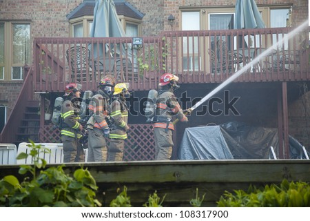 BRAMPTON, ONTARIO -  JULY 20 2012 - Firefighters attempt to douse a house fire burning at 20 Esker Drive in Brampton Ontario on July 20, 2012 - stock photo