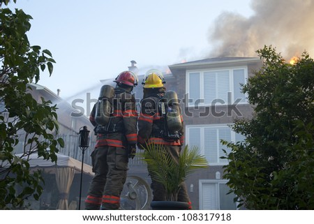 BRAMPTON, ONTARIO -  JULY 20 2012 - Firefighters working to douse a house fire burning at 20 Esker Drive in Brampton Ontario on July 20, 2012