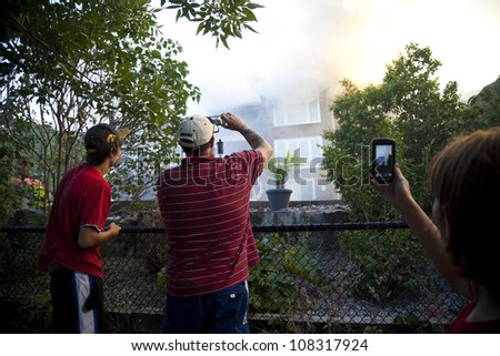 BRAMPTON, ONTARIO -  JULY 20 2012 - Onlookers watch and record a house fire burning at 20 Esker Drive in Brampton Ontario on July 20, 2012 - stock photo
