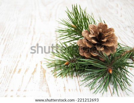 Branch and pine cones on wooden background