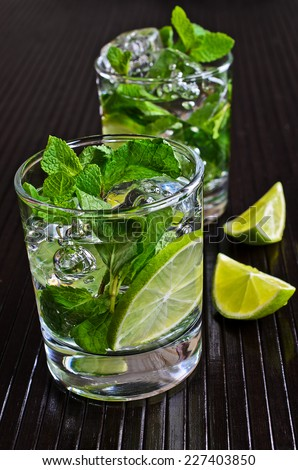 Branch mint, lime and ice in a transparent glass filled with liquid on a black surface - stock photo