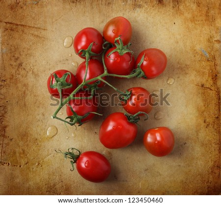 Branch of cherry tomatoes on an old rustic stone chopping board - stock photo