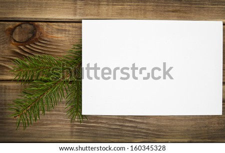 branch of fir-tree and business card on a wooden background - stock photo