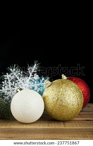 branch of fir-tree, snowflakes and new-year decorations on a black background