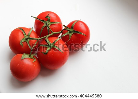 Branch of fresh red tomatoes on light background with shadows and free space for your text.
