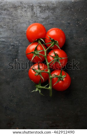 Branch of fresh tomatoes on slate. Food background