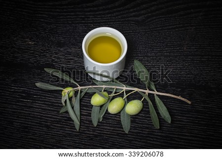 Branch of olive tree with green olive berries and cap of fresh olive oil on a black wooden table or board. Toned. - stock photo