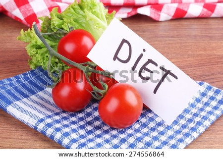 """Branch of red tomatoes and leafy green lettuce on the table. A healthy diet, weight loss. The concept of dieting and healthy eating. Branch of cherry tomatoes. Note The """"Diet"""". Banner, concept. - stock photo"""