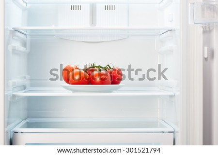 Branch of red tomatoes on white plate in open empty refrigerator. Weight loss diet concept.  - stock photo
