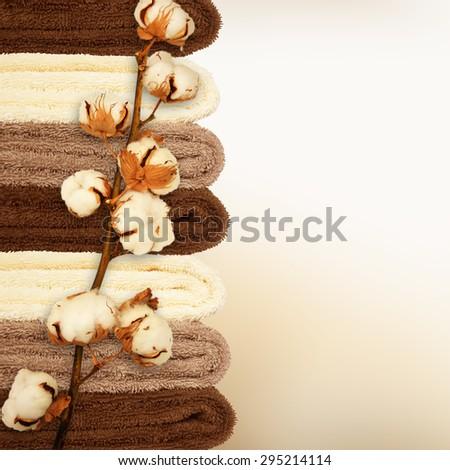 Branch of ripe cotton bolls on multicolor bath towels  - stock photo