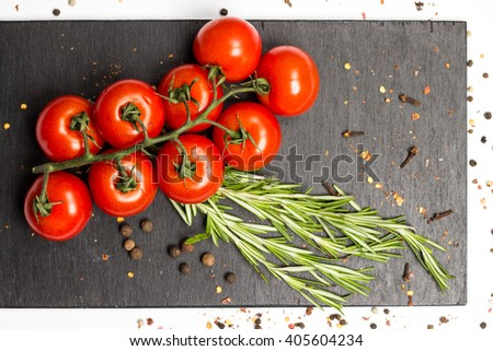 branch of ripe red cherry tomatoes, fresh rosemary, sprinkled with allspice, cloves, on dark wooden board food photography - stock photo