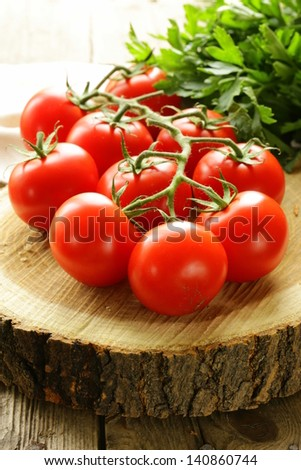 branch of ripe red tomato on a wooden stump - stock photo