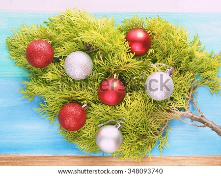 Branch of thuja with silver and red baubles on blue pastel wooden background - stock photo