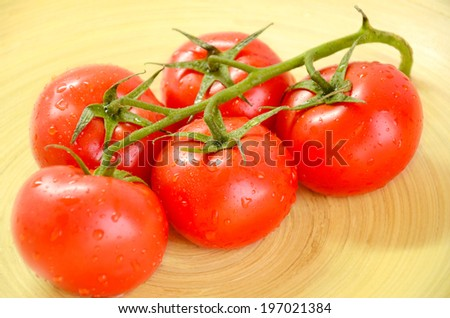branch of tomatoes on a wooden platter closeup