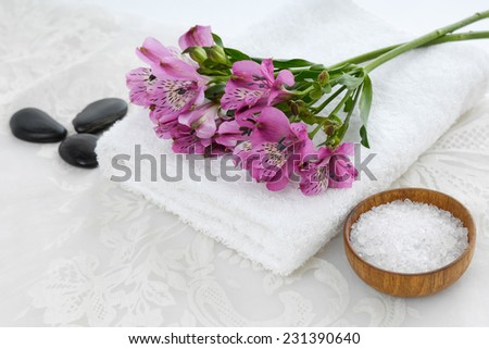 branch pink orchid on towel with stones ,salt in bowl and white lace  - stock photo