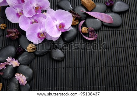 Branch pink orchid with stones and petals on bamboo mat - stock photo