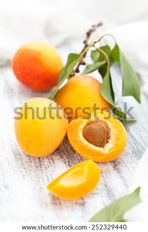 Branch with ripe apricots on white wooden table. - stock photo