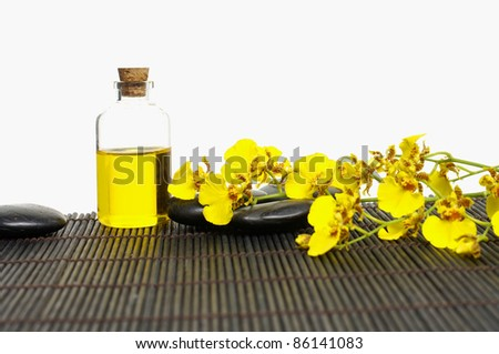 Branch yellow orchid with bottles of essential oil with zen stones on bamboo stick straw mat - stock photo
