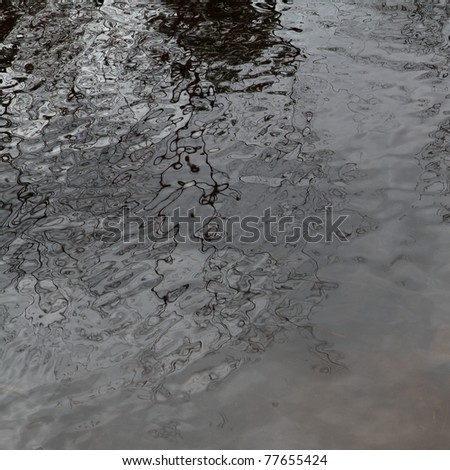 Branches and clouds reflected in a rippled pond surface - stock photo