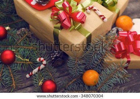 Branches of a Christmas tree on old boards. Gift boxes close-up. Christmas background. Christmas Socks. Christmas decorations. New Year background. Xmax background. Selective focus on a bow-knot - stock photo