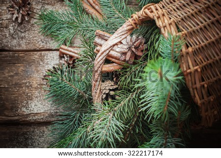 Branches of Blue Fir Tree, Cinnamon and Pine Cones Scattered from Rural Basket on Wooden Table. Top view - stock photo