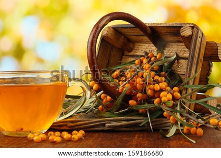 Branches of sea buckthorn with tea and wooden basket on table on bright background - stock photo