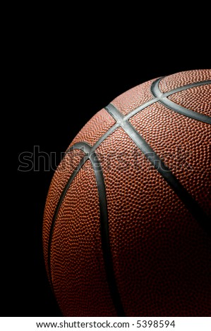 Brand new basketball on black background lit from the side
