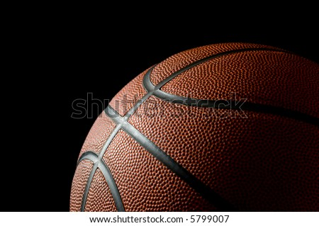 Brand new basketball on black background lit from the side with space for copy above and to the left