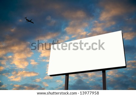 Brand new billboard in the setting sun with a jet flying over - stock photo