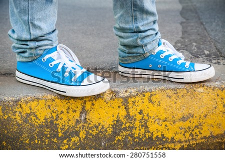 Brand new blue shoes and yellow concrete edge, urban walking theme. Closeup photo with selective focus and shallow DOF - stock photo