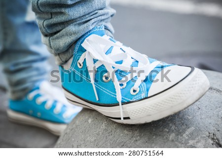 Brand new blue shoes, urban walking theme. Closeup photo with selective focus and shallow DOF - stock photo