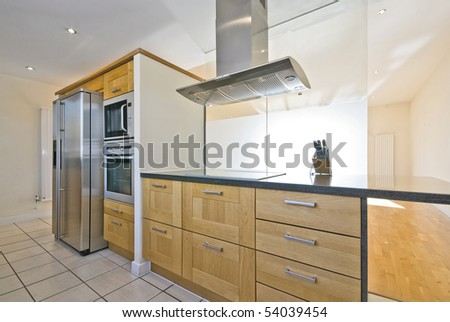 Brand new contemporary open plan kitchen with modern appliances and double American style fridge - stock photo
