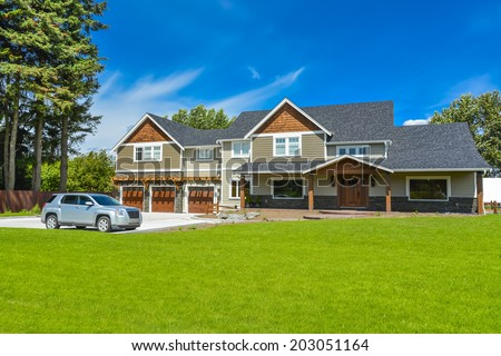 Brand new farmer's house with car parked on driveway in front. Huge family house with three garage door and blue sky background. British Columbia, Canada.  - stock photo
