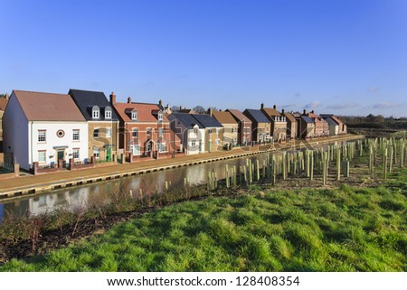 Brand new luxury houses by a canal with trees planted for noise reduction - stock photo
