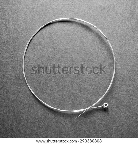 Brand new nickel folk or elctric guitar string. G-string 0.016, isolated on black. in black and white - stock photo