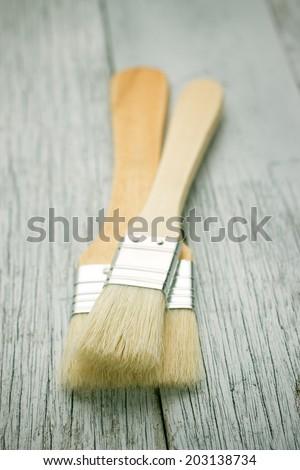 Brand new paint brush on wood background - stock photo