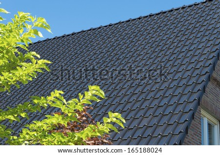 brand new roof top with dark tiles - stock photo