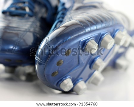 Brand new shiny blue Soccer boots, Football sports shoes with 12 studs, on shiny background - stock photo