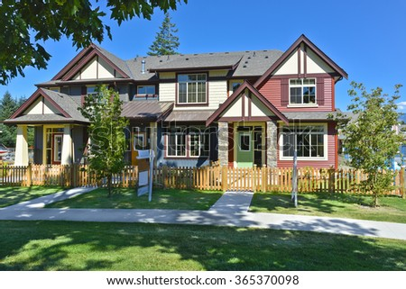 Brand new townhouses on sunny day for sale. Residential houses with green lawn in front and blue sky background. - stock photo
