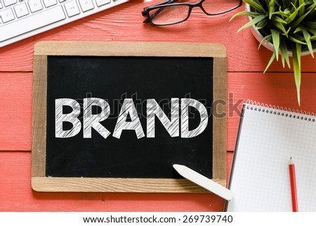 Brand word Handwritten on blackboard. Brand word Handwritten with chalk on blackboard, keyboard,notebook,glasses and green plant on wooden background - stock photo