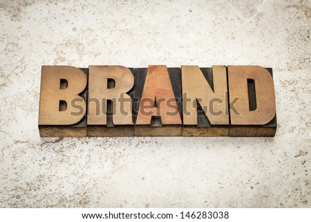 brand word in vintage letterpress wood type on a ceramic tile background - stock photo
