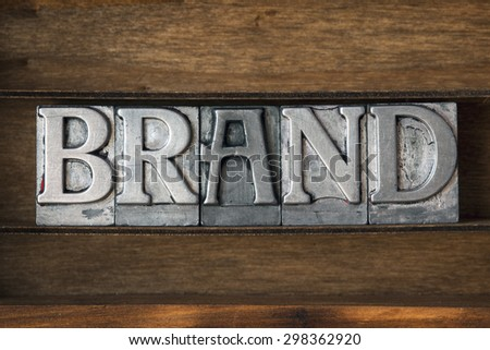 brand word made from metallic letterpress type on wooden tray - stock photo