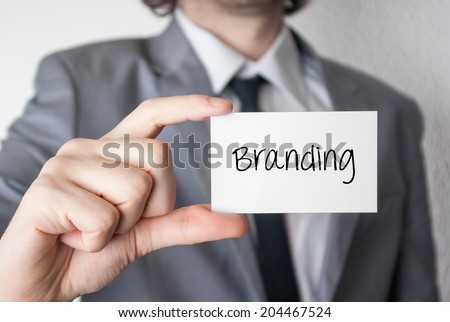 Branding. Businessman in suit with a black tie showing or holding business card