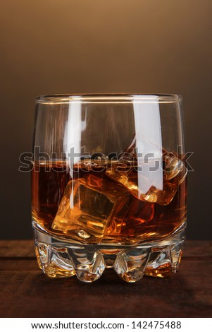 Brandy glass with ice on wooden table on brown background