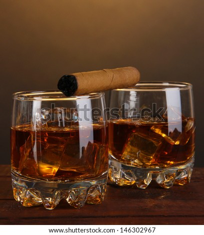 Brandy glasses with ice and cigar on wooden table on brown background