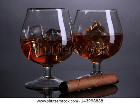 Brandy glasses with ice on grey background - stock photo