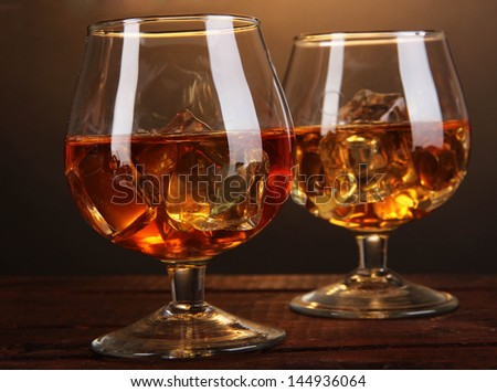 Brandy glasses with ice on wooden table on brown background - stock photo