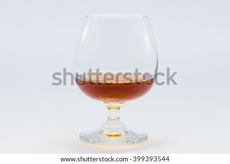 brandy into the glass on white background - stock photo