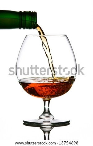 Brandy pouring from green bottle to glass
